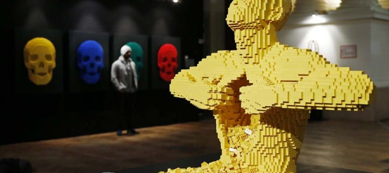 """The art work titled """"Yellow,"""" which is made out of Lego bricks, is seen as a visitor poses next to another Lego art work titled """"Skulls"""" (L) during """"The Art of the Brick"""" exhibition at the Brussels Stock Exchange November 25, 2013. The exhibition featuring large Lego art works by U.S. Lego artist Nathan Sawaya will run till April 21, 2014.  REUTERS/Francois Lenoir (BELGIUM  - Tags: ENTERTAINMENT SOCIETY) ORG XMIT: FLR05"""